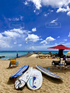砂浜の上に座っている青い傘の写真・画像素材[1386993]