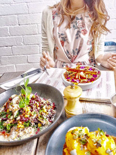食品のプレートをテーブルに座っている女性 - No.806889