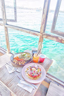 閉じるウィンドウの横のテーブルの上に食べ物のアップの写真・画像素材[877474]