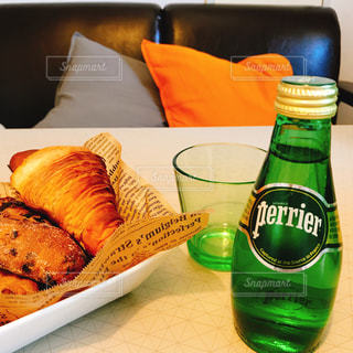 食品のプレートをテーブルの上に座ってガラス ボトルの写真・画像素材[915018]