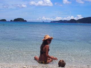 水の体の近くのビーチに座っている男の写真・画像素材[714808]