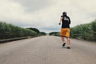 道路の側をスケート ボードに乗って男 - No.891691