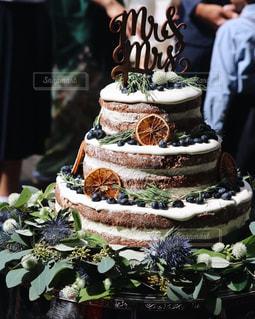 ウエディング ケーキの前に立っている人の写真・画像素材[1229278]