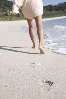 人がビーチで砂の中を歩いての写真・画像素材[1801050]