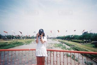 フェンスの横に立っている人の写真・画像素材[1830203]