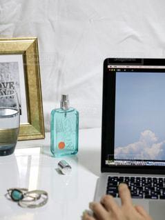 テーブルの上に座っているラップトップコンピュータを使用している人の写真・画像素材[2100847]
