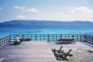 水域の隣に座っている木製のベンチの写真・画像素材[2142224]
