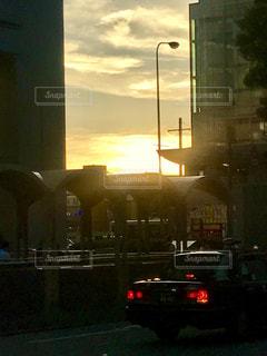 空,建物,夕日,ビル,屋外,大阪,雲,夕焼け,車,道路,車道,オレンジ,都会,道,夕陽,信号待ち