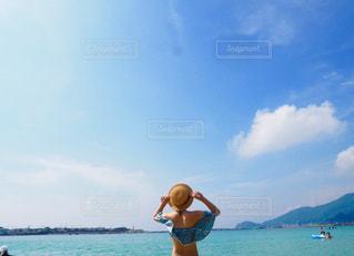 水の体の横に立っている人の写真・画像素材[1403875]