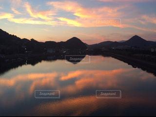 背景の山が付いている水の体に沈む夕日の写真・画像素材[1292500]