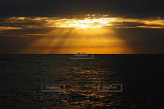 風景,海,空,屋外,太陽,朝日,雲,波,船,水面,水平線,光,キラキラ,柱,日の出,光芒,金色,天使のはしご,イメージ,梯子,ヤコブのはしご,船影