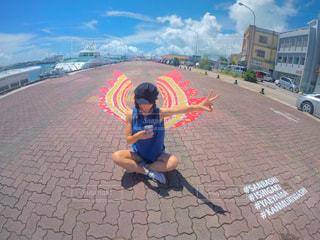 歩道の上に座っている若い男の子の写真・画像素材[771246]
