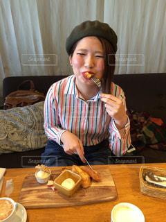 食事のテーブルに座っている女性の写真・画像素材[706118]