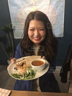 食品のプレートをテーブルに座っている女性の写真・画像素材[706119]