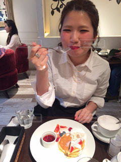 食事のテーブルに座っている女性の写真・画像素材[706122]
