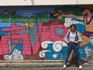 覆われている落書きの壁の横に立っている女性 - No.753330