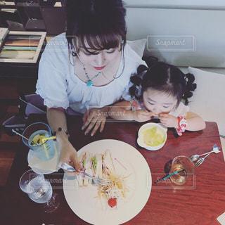 食品のプレートをテーブルに座って人の写真・画像素材[705724]