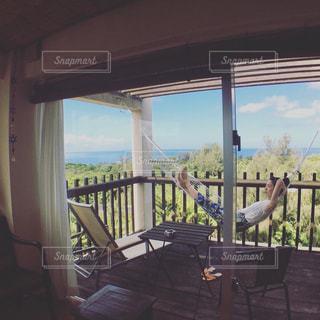窓の前で椅子に座っている人の写真・画像素材[1314530]