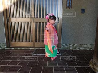 建物の前に立っている女の子の写真・画像素材[1027573]