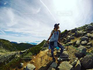 岩が多い丘の上に立っている人の写真・画像素材[772394]