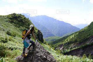 岩が多い丘の上に立っている人の写真・画像素材[772403]