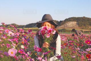 花の前に立っている人の写真・画像素材[890658]