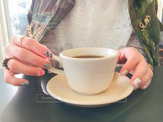 一杯のコーヒーを保持している人の写真・画像素材[916568]