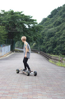 道路の側をスケート ボードに乗って若い男の写真・画像素材[1329162]