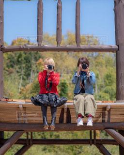 木製のベンチに座っている人々のグループの写真・画像素材[2098374]