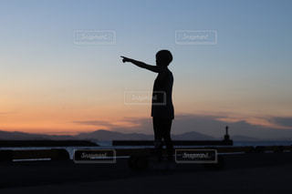 夕日の前に立っている人の写真・画像素材[2965659]