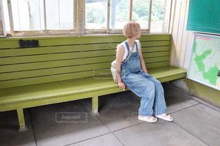 窓の隣のベンチに座っている人の写真・画像素材[3504971]