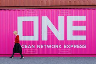 ピンクの壁の前に立っている女性の写真・画像素材[4241473]