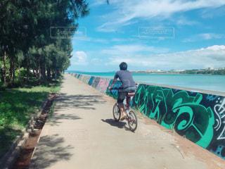 砂浜のビーチで自転車に乗る男の写真・画像素材[1256044]