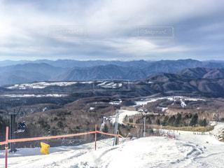 雪に覆われた山に立つ男の写真・画像素材[928731]