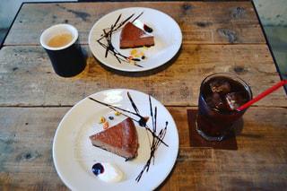 コーヒー カップの横にある皿の上のケーキのスライスの写真・画像素材[1036744]