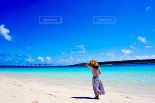 水の体の近くのビーチに立っている人 - No.768974