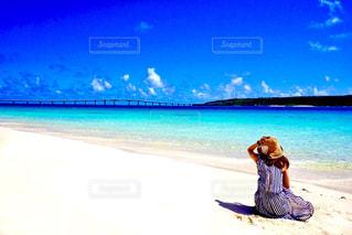 水の体の近くのビーチに座っている男の写真・画像素材[915835]