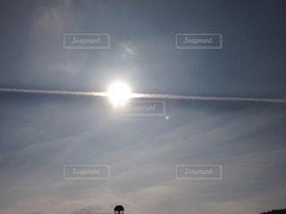 太陽から噴き出す飛行機雲の写真・画像素材[1865986]