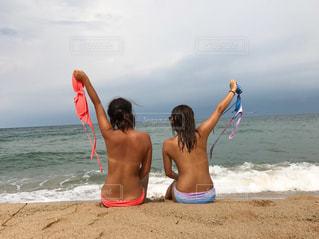 水の体の近くのビーチに立っている人の写真・画像素材[709533]