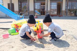 砂の中に座っている小さな男の子の写真・画像素材[817490]