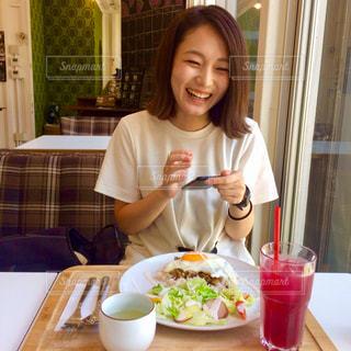 食事のテーブルに座っている女性の写真・画像素材[771166]