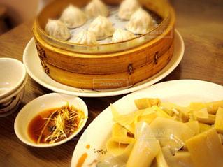 テーブルの上の皿の上に食べ物のボウルの写真・画像素材[927090]