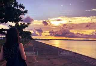 長い髪と背景に夕焼けを持つ人の写真・画像素材[2329192]