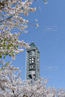 建物の側に時計と大きな背の高い塔の写真・画像素材[1112336]