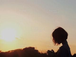 日没の前に立っている男の写真・画像素材[958378]