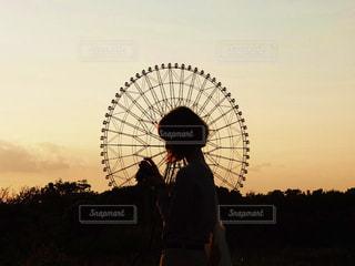 草の中に立っている間凧を保持している男の写真・画像素材[958381]