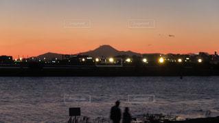 背景の夕日と水体の大型船の写真・画像素材[1272593]