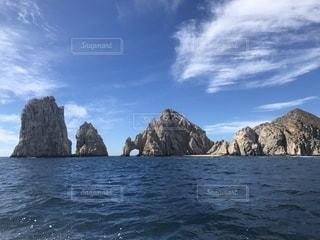 カボ・サン・ルーカスのアーチを背景にした水域の真ん中にある岩の島の写真・画像素材[2332978]
