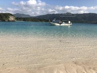 海の隣の砂浜の上に座っているボートの写真・画像素材[2332985]