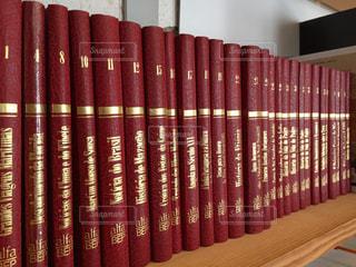 本棚の上に並ぶ赤い本の写真・画像素材[753503]